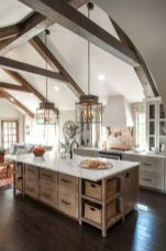 a-dove-grey-vintage-kitchen-with-a-wooden-kitchen-island-printed-tiles-wooden-beams-and-refined-lamps-that-accent-the-attic-ceiling