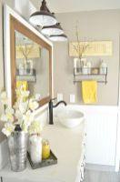 a-farmhouse-bathroom-with-grey-walls-white-furniture-and-appliances-a-mirror-retro-lamps-and-retro-shelves
