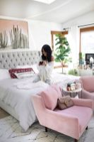 a-fun-feminine-bedroom-with-a-large-grey-bed-pink-chairs-statement-plants-a-cactus-artwork-and-boho-pillows