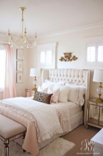 a-glam-girlish-bedroom-with-an-upholstered-bed-mirrored-nightstands-and-a-bench-a-crystal-chandelier-and-touches-of-light-pink