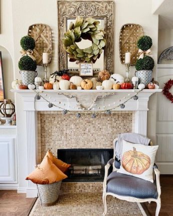 a-lovely-modern-farmhouse-Thanksgiving-mantel-with-lots-of-pumpkins-of-various-sizes-greenery-topiaries-a-leaf-wreath-and-woden-baskets