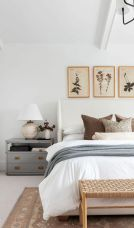 a-mid-century-modern-bedroom-with-a-grey-nightstand-a-woven-bench-a-white-bed-grey-and-white-bedding