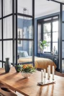 a-modern-bedroom-with-blue-walls-a-bed-some-statement-plants-and-vases-and-glass-walls-all-over-to-maximize-the-daylight