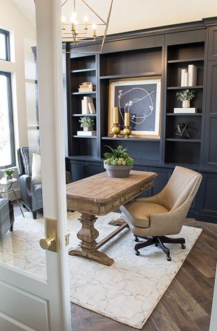 a-modern-farmhouse-home-office-with-a-navy-storage-unit-that-takes-a-whole-wall-a-wooden-desk-leather-chairs-and-a-refined-gold-chandelier