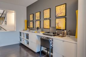 a-modern-home-office-with-a-grey-accent-wall-a-yellow-gallery-wall-of-floral-prints-a-large-desk-with-storage-and-a-grey-chair