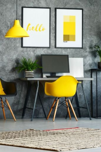 a-modern-home-office-with-a-grey-wallpaper-wall-a-small-desk-a-black-and-a-yellow-chair-a-yellow-pendant-lamp-and-some-bold-prints
