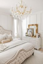 a-neutral-Versaille-inspired-bedroom-with-refined-furniture-a-crystal-chandelier-gold-framed-art-and-mirrors-and-layered-bedding