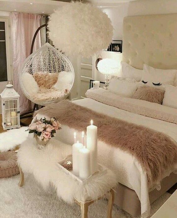 a-neutral-and-blush-feminine-bedroom-with-a-white-upholstered-bed-a-furry-bench-a-suspended-chair-and-a-feather-chandelier