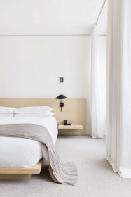 a-neutral-and-welcoming-zen-bedroom-with-light-colored-wooden-bed-and-nightstands-black-sconces-and-white-textiles