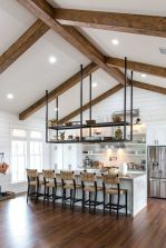 a-neutral-farmhouse-kitchen-clad-with-beadboard-with-white-cabinetry-woven-stools-wooden-beams-and-a-pendant-storage-unit