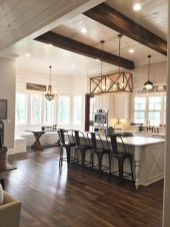 a-neutral-farmhouse-kitchen-with-grey-cabinetry-dark-chairs-and-a-table-pendant-lamps-and-a-wooden-chandelier