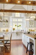 a-neutral-modern-farmhouse-kitchen-with-light-colored-wooden-beams-wooden-chairs-and-countertops-that-soften-the-look