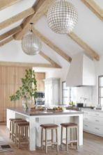 a-neutral-modern-farmhouse-kitchen-with-white-cabinets-and-a-kitchen-island-a-marble-backsplash-light-colored-wooden-beams-and-sphere-lamps