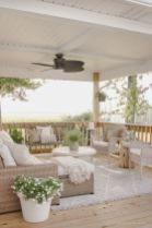 a-neutral-rustic-seaside-terrace-with-light-colored-wicker-furniture-white-upholstery-and-textiles-and-potted-blooms-and-greenery