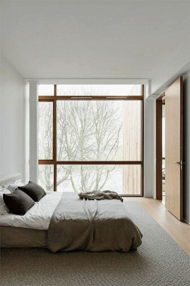 a-neutral-zen-bedroom-with-a-bed-right-on-the-floor-and-a-glazed-wall-to-enjoy-the-views-plus-neutral-linens-and-bedding
