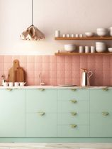 a-pretty-contemporary-kitchen-with-mint-cabinetry-and-gold-handles-patterned-and-textural-pink-tiles-a-copper-geometric-pendant-lamp