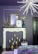 a-purple-and-white-bedroom-with-a-faux-fireplace-some-gold-candleholders-and-a-mirror-ina-frame-a-chandelier-with-bulbs-and-floral-bedding