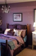 a-purple-bedroom-with-a-forged-bed-purple-and-pink-bedding-a-crystal-chandelier-and-some-artworks