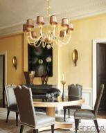 a-refined-and-chic-grey-and-yellow-dining-room-with-yellow-paneled-walls-a-round-table-grye-chairs-a-chic-chandelier-and-a-marble-fireplace