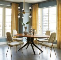 a-refined-and-elegant-grey-and-yellow-dining-room-with-grey-walls-yellow-curtains-a-round-dining-table-neutral-chairs-and-a-pretty-chandelier