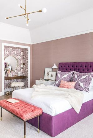a-refined-bedroom-with-mauve-walls-a-wallpaper-makeup-niche-a-round-mirror-a-metallic-chandelier-and-a-purple-bed
