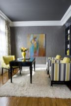 a-refined-home-office-with-grey-walls-and-a-ceiling-a-lemon-yellow-chair-and-striped-grey-and-yellow-ones-grey-bookcases-and-a-refined-desk