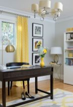 a-refined-mid-century-modern-home-office-with-light-grey-walls-a-dark-desk-and-a-dark-chair-a-brass-lamp-and-a-grey-and-yellow-printed-rug