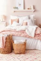 a-relaxed-feminine-bedroom-with-blush-walls-simple-furniture-white-and-pink-bedding-a-shelf-with-art-and-a-couple-of-baskets