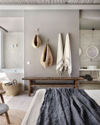 a-relaxed-zen-bedroom-united-with-a-bathroom-with-stone-and-concrete-walls-a-wooden-bench-neutral-bedding-and-baskets-for-storage