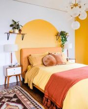 a-retro-bedroom-with-a-yellow-accent-wall-and-a-color-block-one-with-an-orange-bed-pretty-nightstands-vintage-lamps-and-a-boho-rug