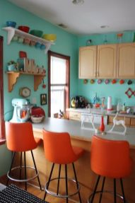 a-retro-blue-ktichen-with-orange-stools-and-colorful-tableware-plus-mugs-is-a-very-stylish-and-bold-space