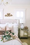 a-romantic-and-feminine-bedroom-with-a-neutral-upholstered-bed-blush-and-white-bedding-a-crystal-chandelier-and-a-mirror-nightstand