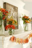 a-rustic-chic-Thanksgiving-mantel-with-bold-blooms-and-greenery-arrangements-a-wooden-sign-and-paper-fall-leaf-garland