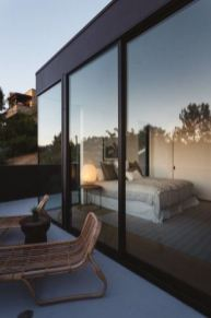 a-simple-contemporary-bedroom-with-a-bed-a-nightstand-with-a-lamp-and-glass-walls-plus-an-entrance-to-the-terrace-is-very-cool