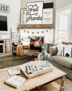 a-simple-farmhouse-Thanksgiving-mantel-with-a-pinecone-garland-several-signs-and-pillows-and-a-blanket