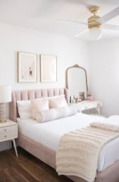 a-simple-feminine-bedroom-with-a-blush-bed-white-nightstands-a-mirror-in-a-brass-frame-and-cute-artworks