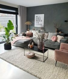 a-spring-ready-living-room-with-a-grey-sofa-a-pink-chair-pillows-and-blankets-some-branches-in-vases-and-a-statement-plant