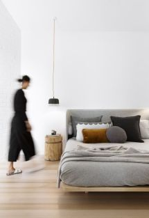 a-stylish-and-neutral-zen-bedroom-with-a-comfy-wooden-bed-grey-and-black-bedding-a-wooden-nightstand-and-a-pendant-lamp