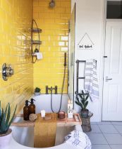 a-stylish-bathroom-with-yellow-tiles-a-grey-tile-floor-white-walls-and-applainces-and-potted-plants-looks-wow