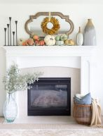 a-stylish-modern-Thanksgiving-mantel-with-a-leaf-wreath-neutral-and-pastel-pumpkins-and-large-vases