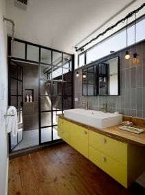 a-super-chic-bathroom-with-grey-tiles-a-floating-yellow-vanity-a-wooden-countertop-a-shower-space-with-a-framed-glass-space-divider
