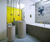 a-super-contemporary-bathroom-with-rough-concrete-walls-and-a-tub-clad-with-it-catchy-free-standing-sinks-ceiling-lamps-and-a-yellow-statement-wall