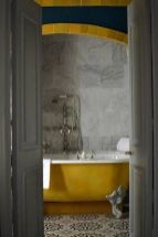 a-vintage-bathroom-clad-with-grye-marble-tiles-and-patterned-ones-a-yellow-clawfoot-tub-elegant-fixtures-is-very-chic