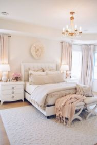 a-welcoming-feminine-bedroom-in-neutrals-and-blush-with-an-upholstered-bed-neutral-furniture-a-crystal-chandelier-and-touches-of-blush