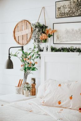 a-welcoming-spring-bedroom-in-neutrals-with-pretty-artworks-greenery-and-blooms-a-wall-sconce-printed-bedding