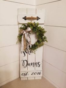 a-white-sign-with-a-greenery-wreath-burlap-and-plaid-bows-a-twine-handle-is-a-chic-idea-for-a-rustic-space