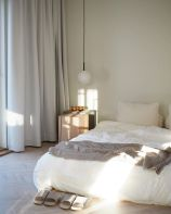 a-zen-like-bedroom-with-a-bed-right-on-the-floor-a-wooden-nightstand-a-pendant-lamp-and-neutral-bedding-is-chic