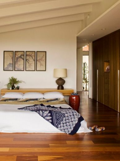 an-Asian-zen-bedroom-with-a-bed-on-the-floor-a-floating-console-at-the-head-a-gallery-wall-and-bright-bedding