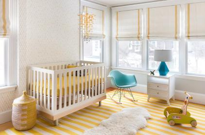 an-airy-nursery-with-white-walls-a-striped-yellow-rug-a-crib-with-yellow-bedding-some-toys-and-Roman-shades-with-yellow-stripes