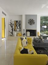 an-elegant-living-room-with-a-grey-and-yellow-furniture-a-fireplace-printed-rugs-and-pillows-and-a-pretty-artwork